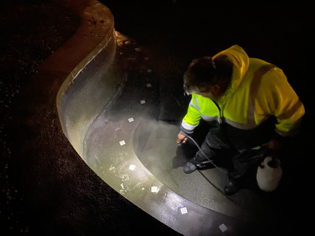 A member of the Clean Team power washes a soaking pool