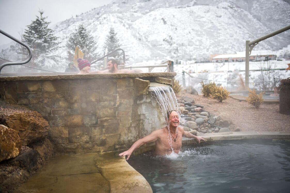 Man relaxing under waterfall in winter at Iron Mountain Hot Springs